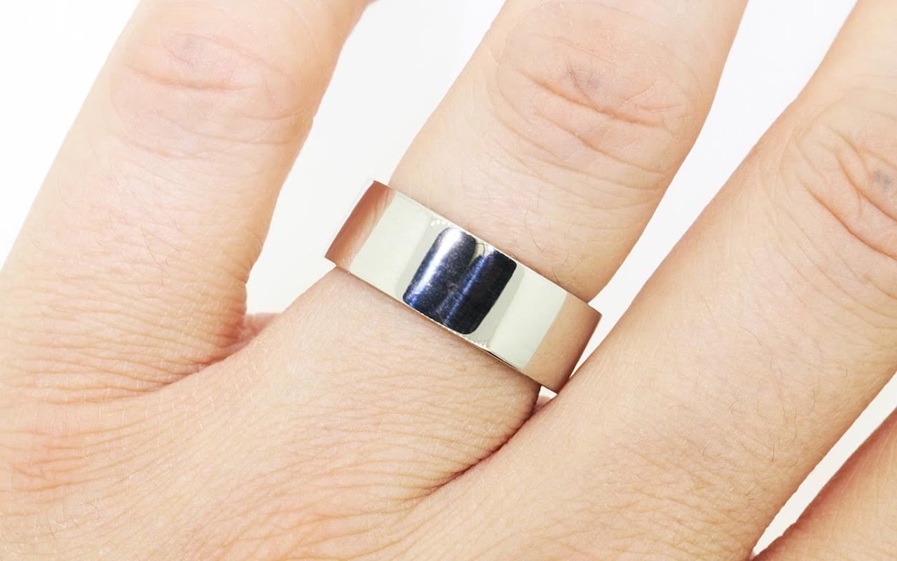 8mm wide flat wedding band in 14k white gold.  Polished finish.  Modeled on a hand.