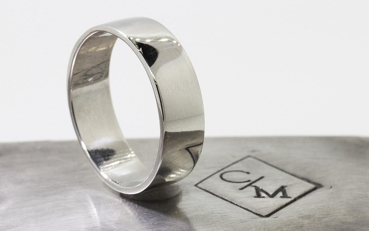 14k white gold men's flat wedding band on metal background with Chinchar/Maloney logo. Standing view