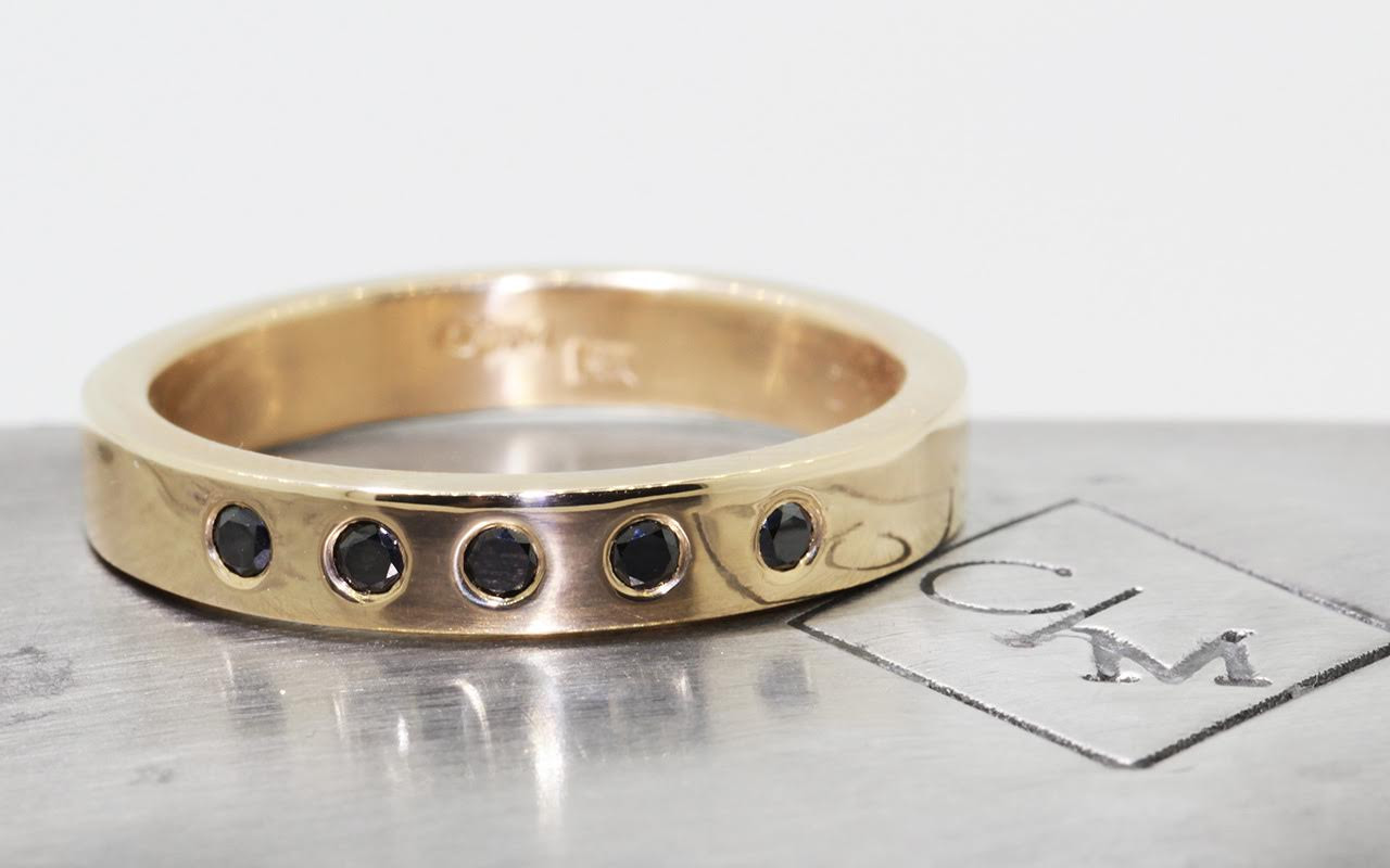 4mm wide flat wedding band in 14k yellow gold.  Five small round black diamonds set into the band.  Front view metal background with Chinchar/Maloney logo.