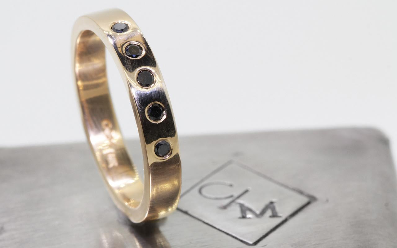 4mm wide flat wedding band in 14k yellow gold.  Five small round black diamonds set into the band.  Side view metal background with Chinchar/Maloney logo.