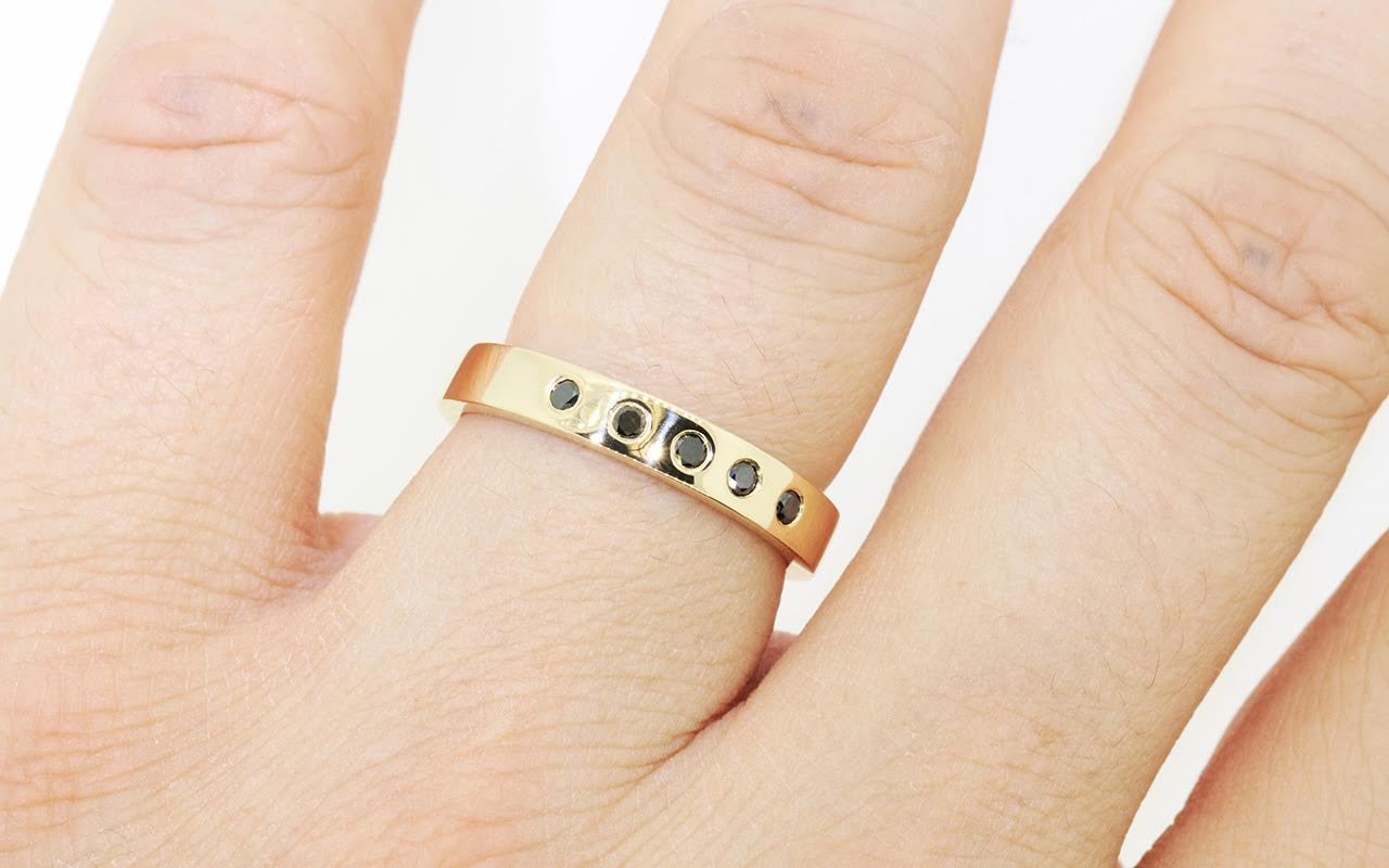 4mm wide flat wedding band in 14k yellow gold.  Five small round black diamonds set into the band.  Modeled on a hand.