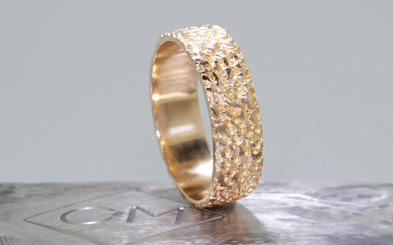 14k yellow gold mens wedding band with stippled texture on metal background with Chinchar/Maloney logo.