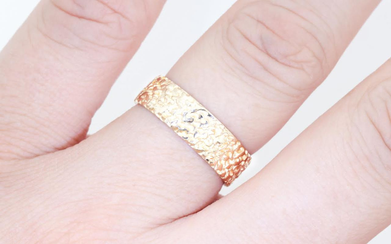 14k yellow gold mens wedding band with stippled texture modeled on hand.
