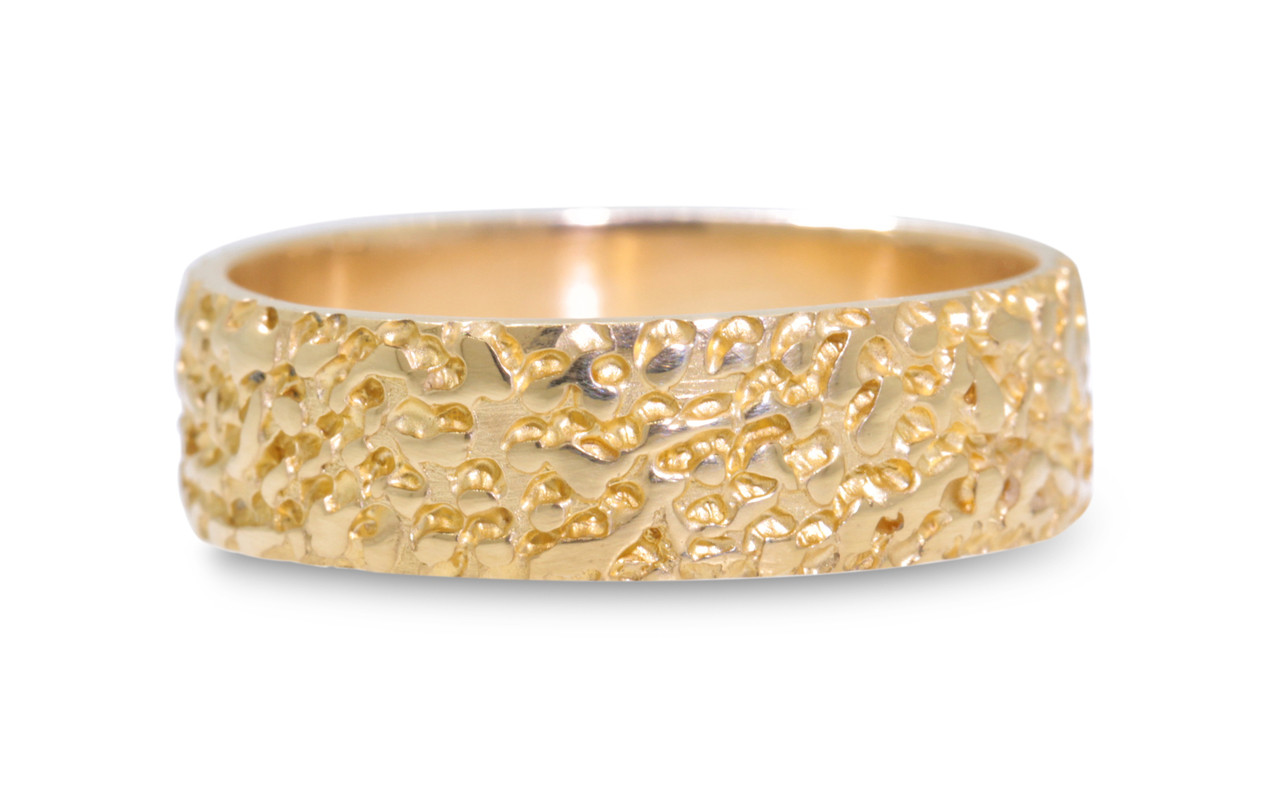 14k yellow gold mens wedding band with stippled texture on white back ground.