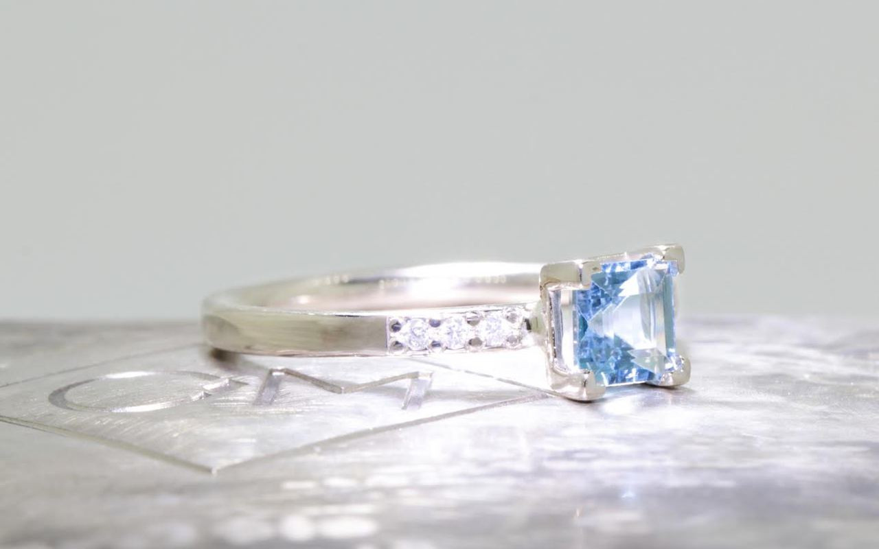 .58 carat aquamarine in  14k white gold six 1.2mm brilliant white diamonds set in band 3/4 view on metal background with Chinchar/Maloney logo