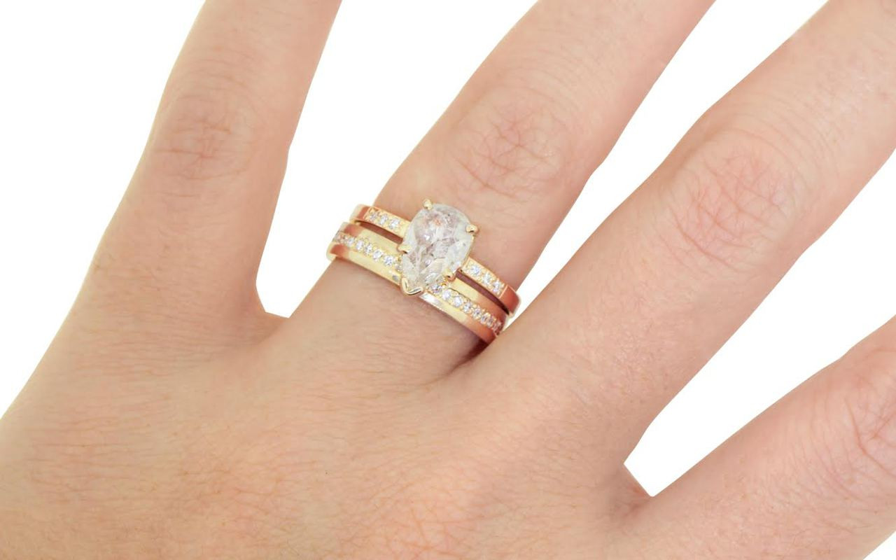 Wedding band in 14k yellow gold with white diamonds bead pave set down the center in eternity style.  Modeled on a hand and stacked with a diamond ring.