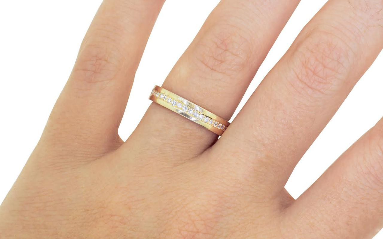 Wedding band in 14k yellow gold with white diamonds bead pave set down the center in eternity style.  Modeled on a hand.