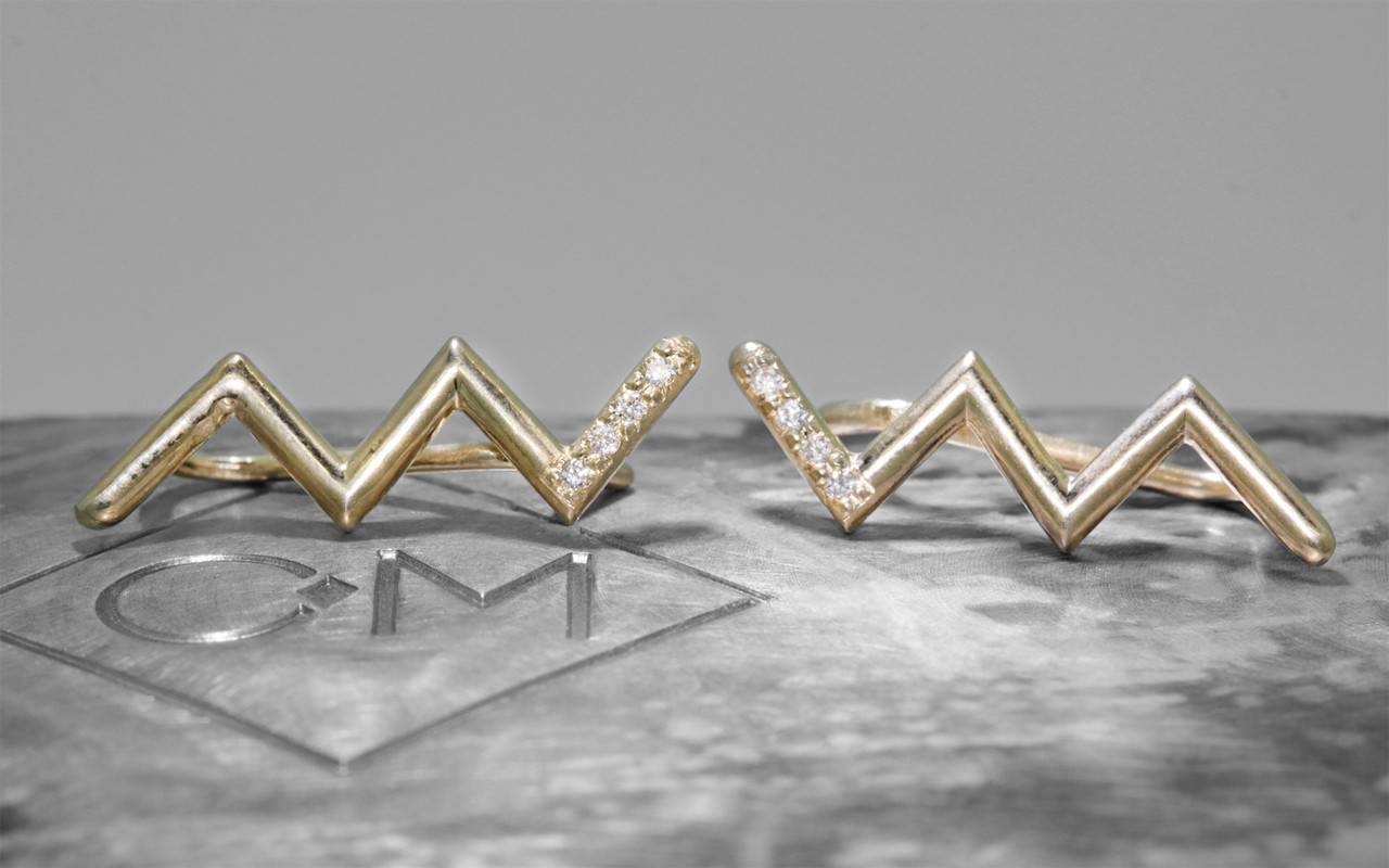 Ear climbers in zig zag shape in 14k yellow gold.  Small brilliant round white diamonds are set last section of the earring.  Front view of pair of earrings on metal background with Chinchar/Maloney logo.