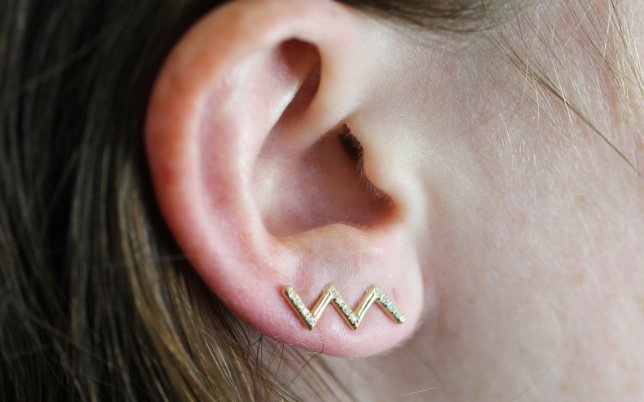Ear climbers in zig zag shape in 14k yellow gold.  Small brilliant round white diamonds are set in three sections of the earring. Modeled on an ear.  Earring is in ear climber position.