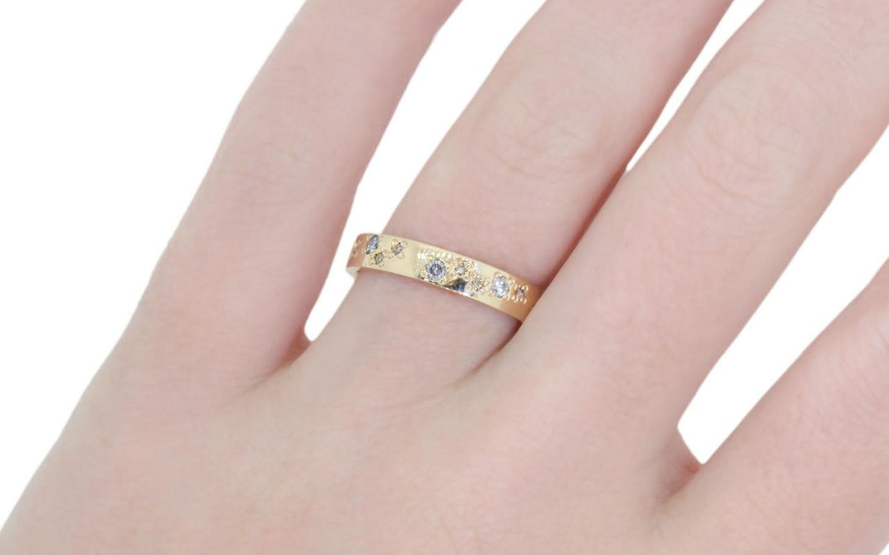 14k yellow gold wedding band with brilliant gray diamonds and brilliant, white diamonds bead set in organic pattern around the entire ring. Modeled on a hand
