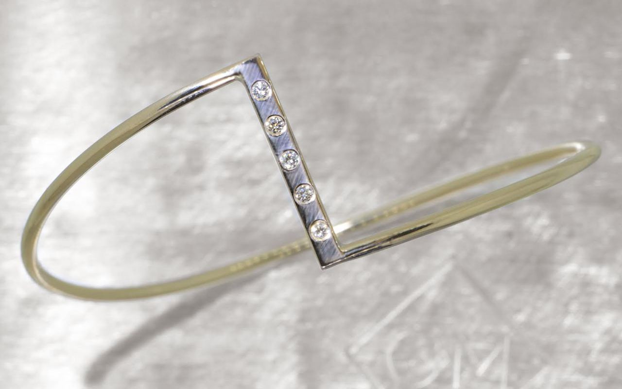 Bracelet in 14k yellow gold in zig-zag shape.  Five 2mm brilliant white diamonds are set in the center bar of the bracelet.  Front view on a metal background with Chinchar/Maloney logo.