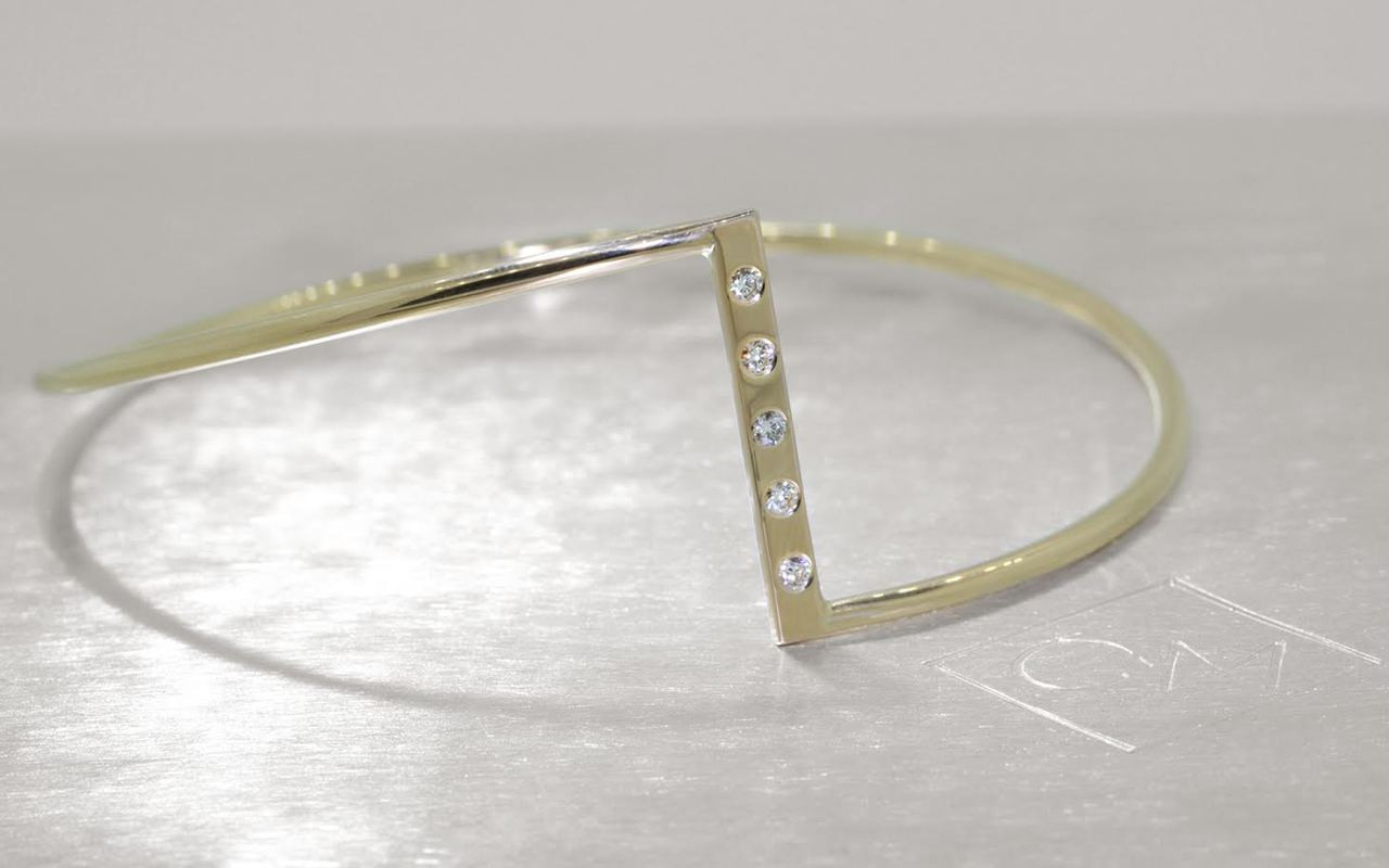 Bracelet in 14k yellow gold in zig-zag shape.  Five 2mm brilliant white diamonds are set in the center bar of the bracelet.  3/4 view on a metal background with Chinchar/Maloney logo.