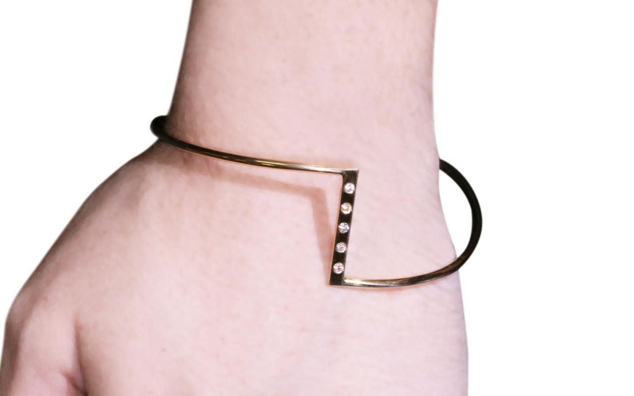Bracelet in 14k yellow gold in zig-zag shape.  Five 2mm brilliant white diamonds are set in the center bar of the bracelet.  Modeled on a wrist.