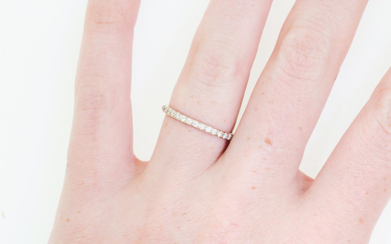14k white gold wedding band with 16 brilliant white pave diamonds half way around band modeled on hand