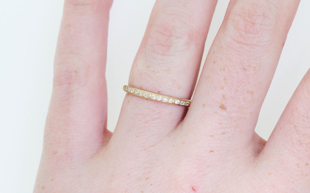 14k yellow gold wedding band with 16 brilliant white pave diamonds half way around band modeled on hand