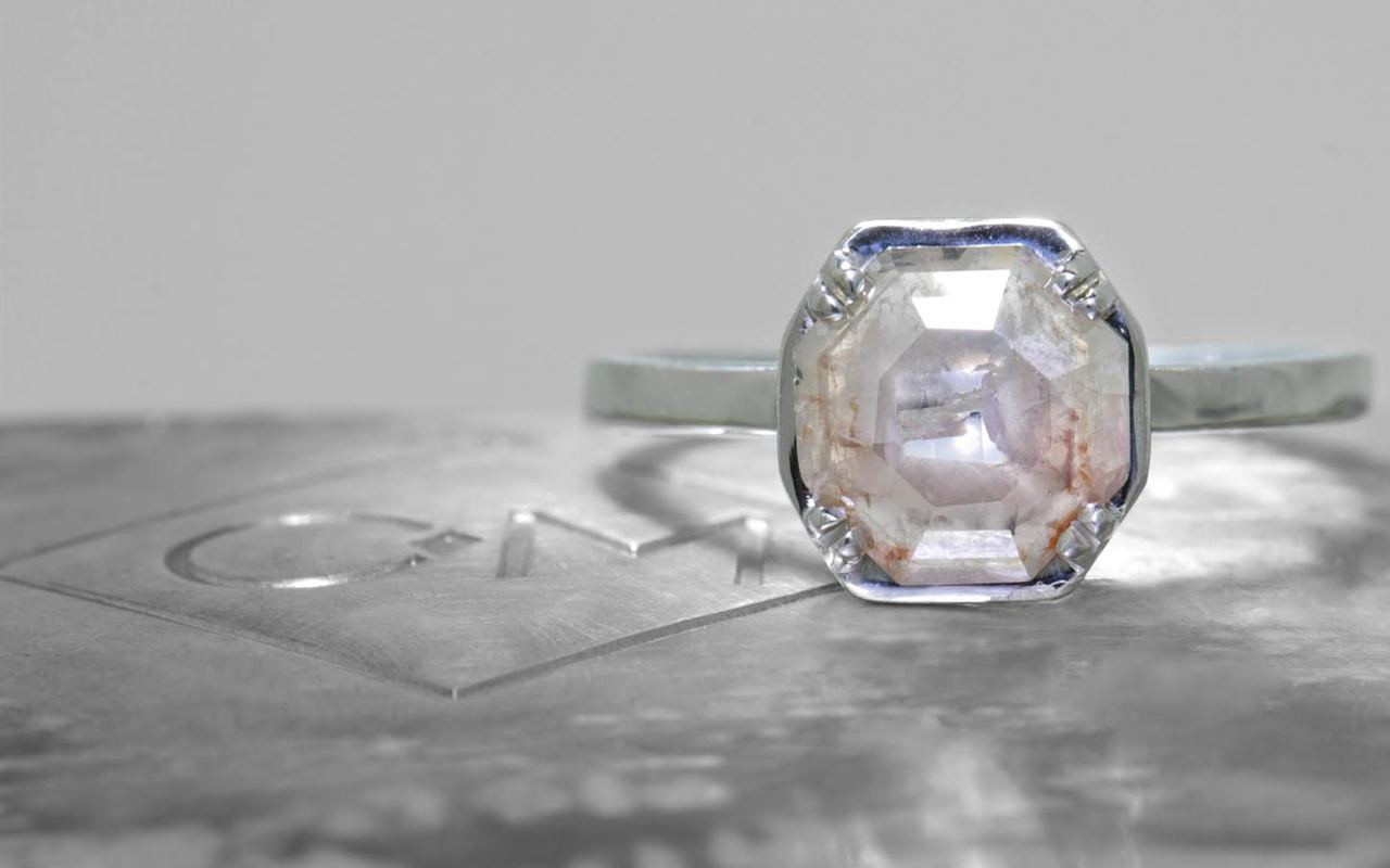 MAROA .98 carat octagon, rose-cut, gray and white diamond ring set in our signature square setting, set in 14k white gold. with four 1.2mm in each corner of main setting. Shown on metal background with Chinchar/Maloney logo