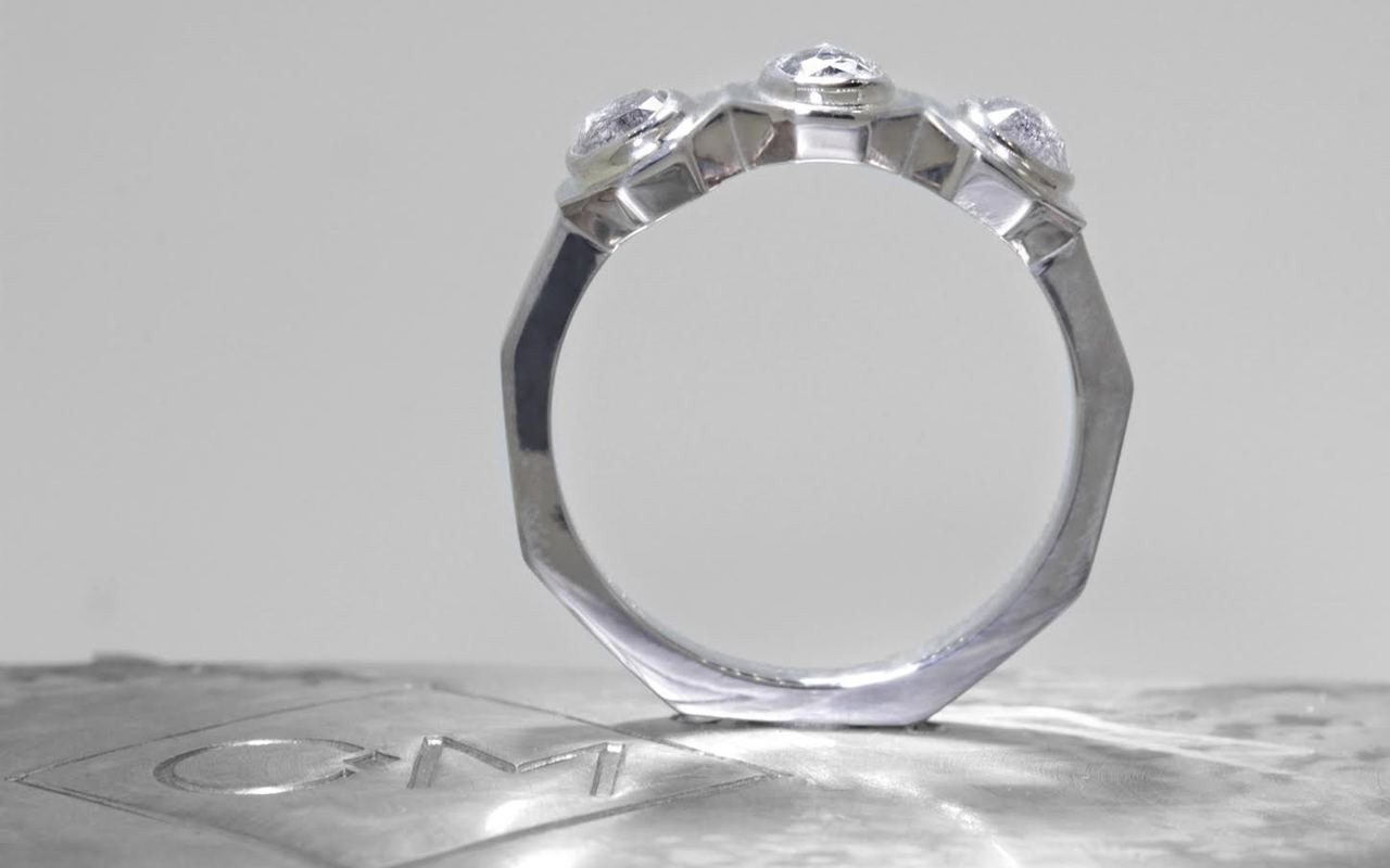 14k white gold ring with three salt and pepper rose cut diamonds bezel set in a rose.  The shape of each setting is octagonal.  On metal background with Chinchar/Maloney logo.  Ring is standing up to show the shape of the band is octagonal.