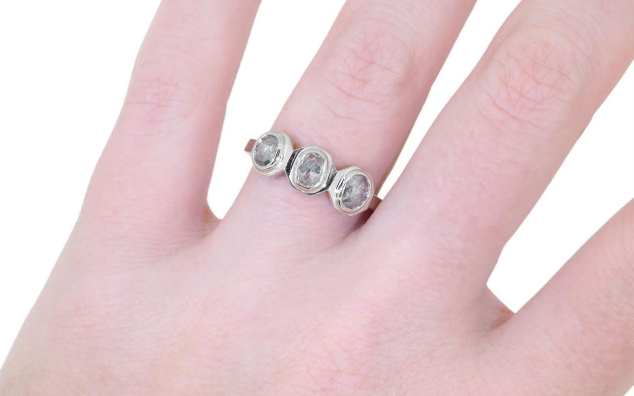 14k white gold ring with three salt and pepper rose cut diamonds bezel set in a rose.  The shape of each setting is octagonal.  Modeled on a hand.
