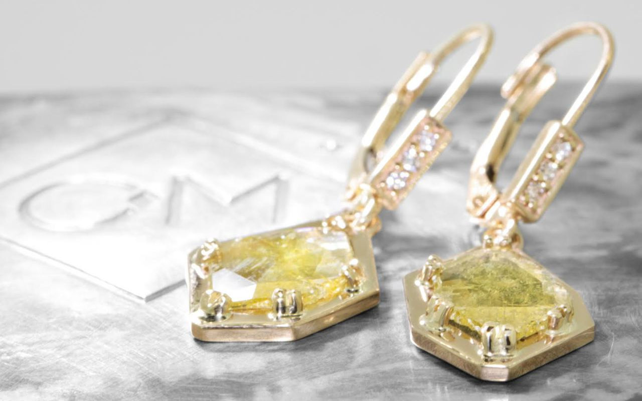 ASKJA 14k yellow gold dangle earrings with 1.11 carat free form green diamonds prong set in geometric 14k yellow gold setting. Three brilliant white diamonds set into front of lever back. Shown on metal background with Chinchar/Maloney logo