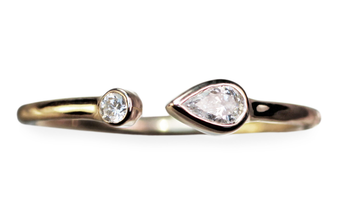 Open cuff ring in 14k yellow gold with .12 carat pear shaped white diamond and a 2mm brilliant round white diamond.  Front view on white background.