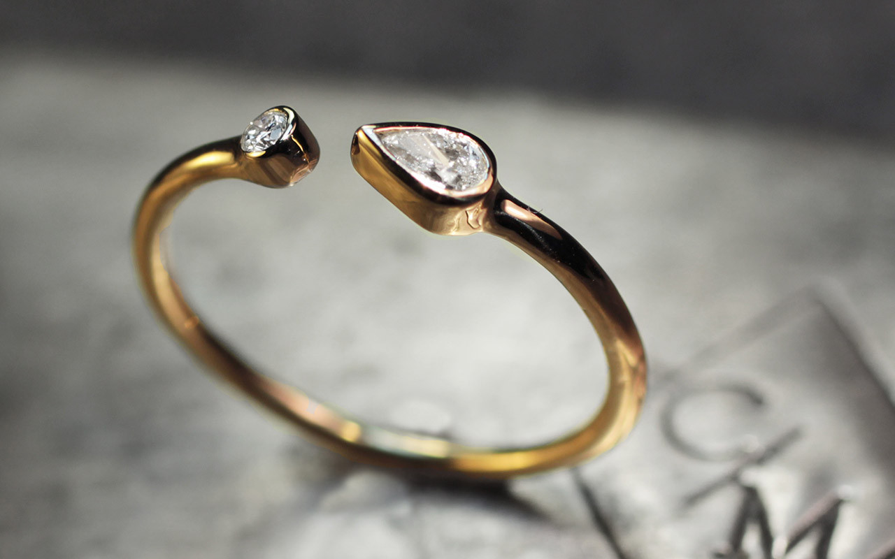 Open cuff ring in 14k yellow gold with .12 carat pear shaped white diamond and a 2mm brilliant round white diamond.  3/4 side view on metal background with Chinchar/Maloney logo.