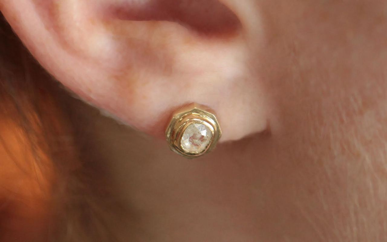 ASKJA 14k yellow gold hexagon stud earrings with round rose cut .71 carat icy white diamonds bezel set. Modeled on ear.