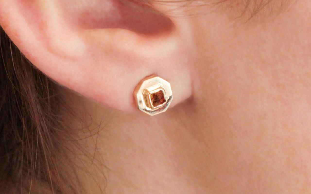 ASKJA 14k yellow gold hexagon earrings with bezel set .44 carat cognac diamonds. Modeled on ear.