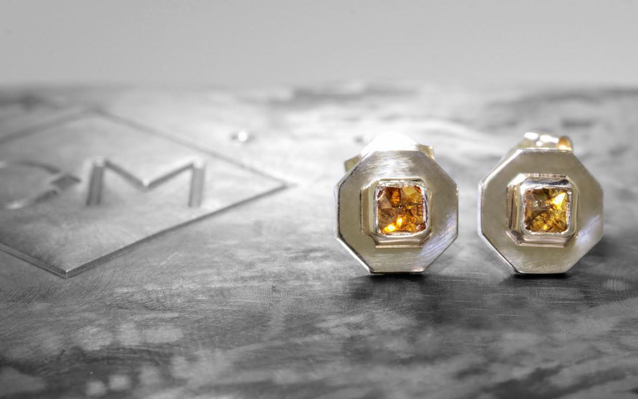 ASKJA 14k yellow gold hexagon earrings with bezel set .44 carat cognac diamonds. On metal background with Chinchar/Maloney logo.