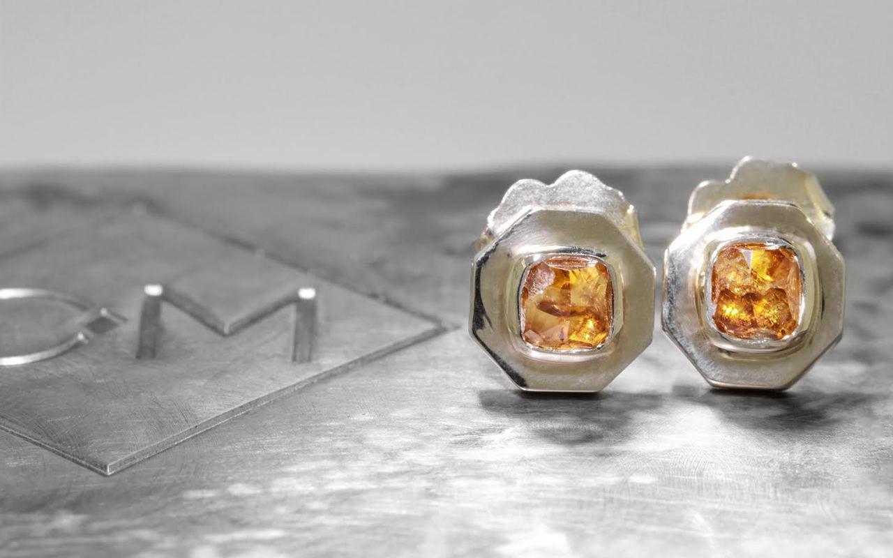 ASKJA 14k yellow gold hexagon stud earrings with bezel set .66 carat honey diamonds. On metal background with Chinchar/Maloney logo. Side view