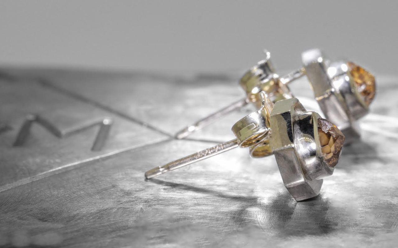 ASKJA 14k yellow gold hexagon stud earrings with bezel set .66 carat honey diamonds. On metal background with Chinchar/Maloney logo