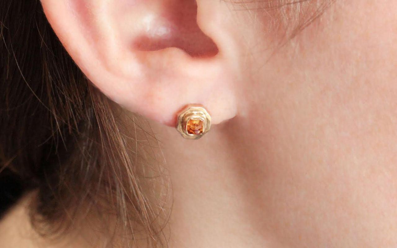 ASKJA 14k yellow gold hexagon stud earrings with bezel set .66 carat honey diamonds. Modeled on ear.