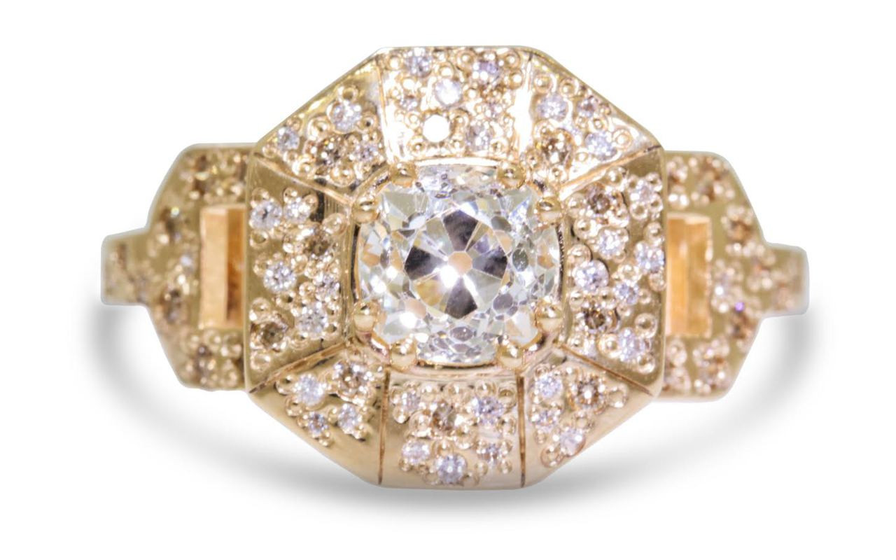 Vesuvio ring in 14k yellow gold.  1.14 carat white center diamond, cushion brilliant cut.  Halo and buckle band are covered in organic brilliant champagne, gray, white pave.  Front view on a white background.