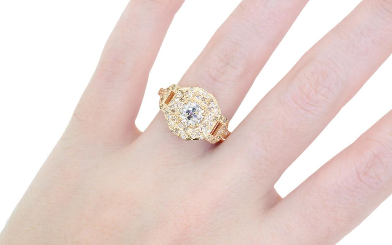 Vesuvio ring in 14k yellow gold.  1.14 carat white center diamond, cushion brilliant cut.  Halo and buckle band are covered in organic brilliant champagne, gray, white pave.  Modeled on a hand.