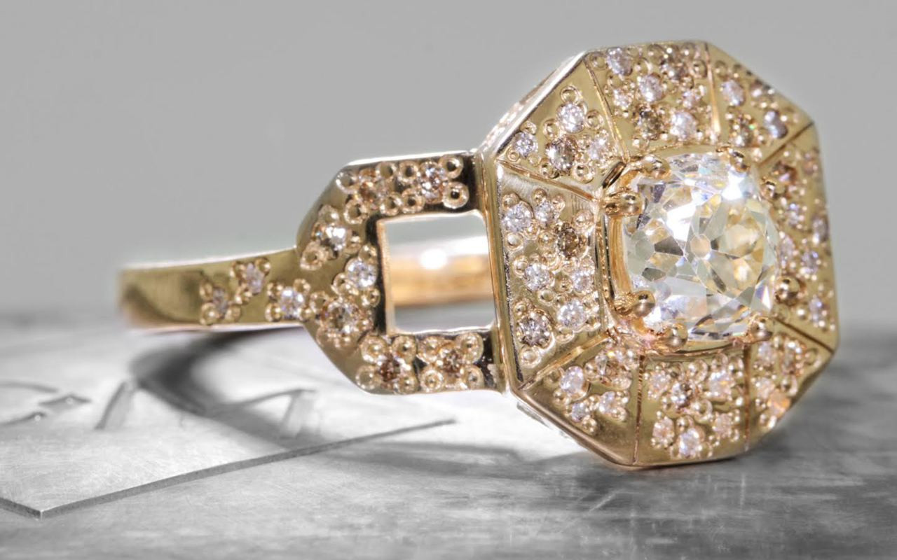 Vesuvio ring in 14k yellow gold.  1.14 carat white center diamond, cushion brilliant cut.  Halo and buckle band are covered in organic brilliant champagne, gray, white pave.  3/4 view on a metal background with Chinchar/Maloney logo.