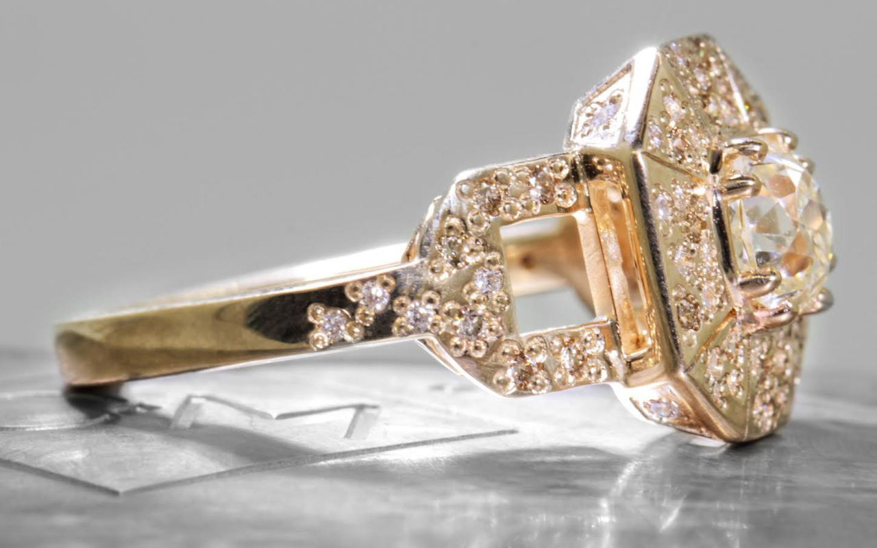 Vesuvio ring in 14k yellow gold.  1.14 carat white center diamond, cushion brilliant cut.  Halo and buckle band are covered in organic brilliant champagne, gray, white pave.  Side view on a metal background with Chinchar/Maloney logo.