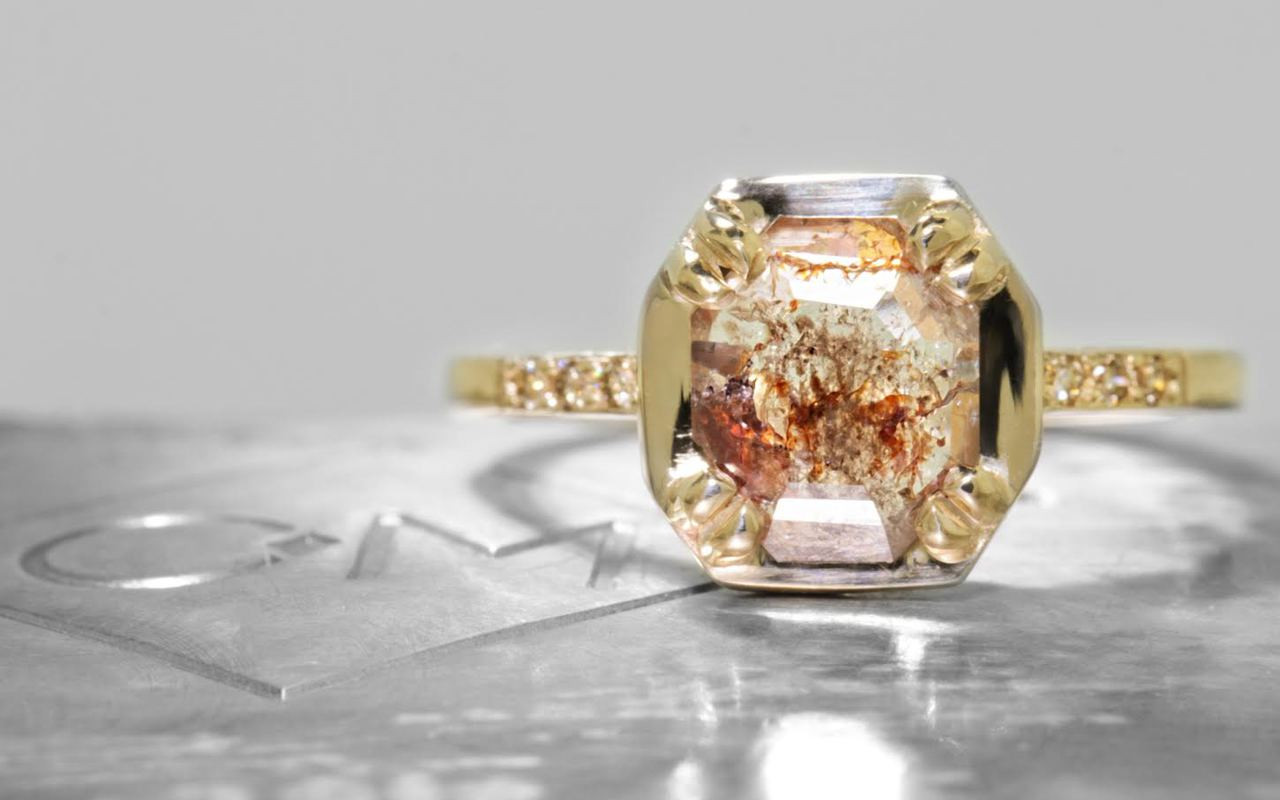 AIRA .62 carat round rose cut icy white diamond prong set in 14k yellow gold geometric octangular setting. Six 1.2mm brilliant champagne diamonds set in 14k yellow gold band. New Classic Collection. On metal background with Chinchar/Maloney logo.