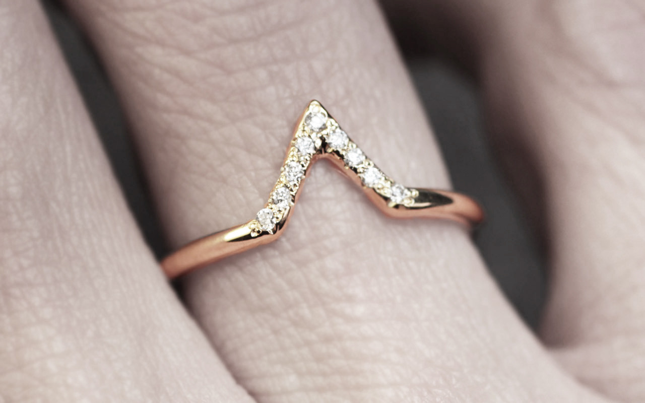 Diamond band in 14k yellow gold.  Center is in triangle shape and set with small, round brilliant white diamonds.  Modeled on a hand.