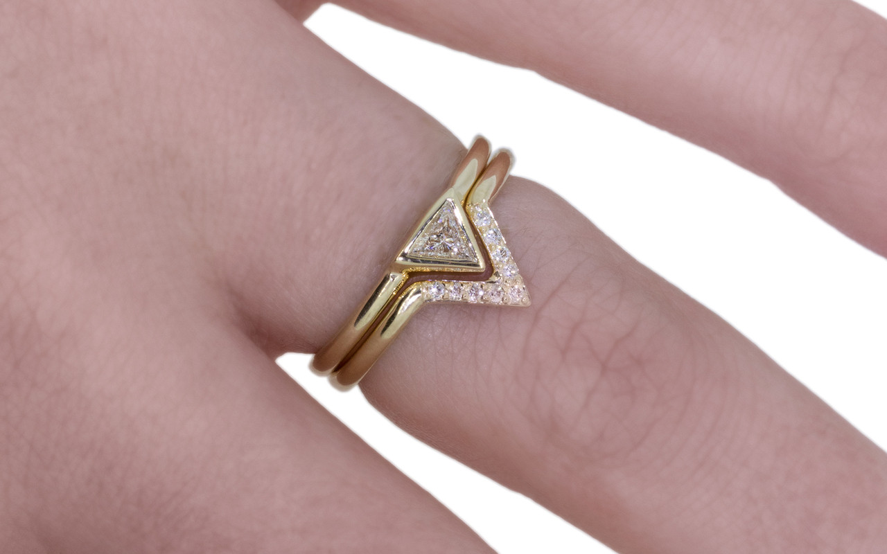 Diamond band in 14k yellow gold.  Center is in triangle shape and set with small, round brilliant white diamonds.  Modeled on a hand with trillion diamond engagement ring.