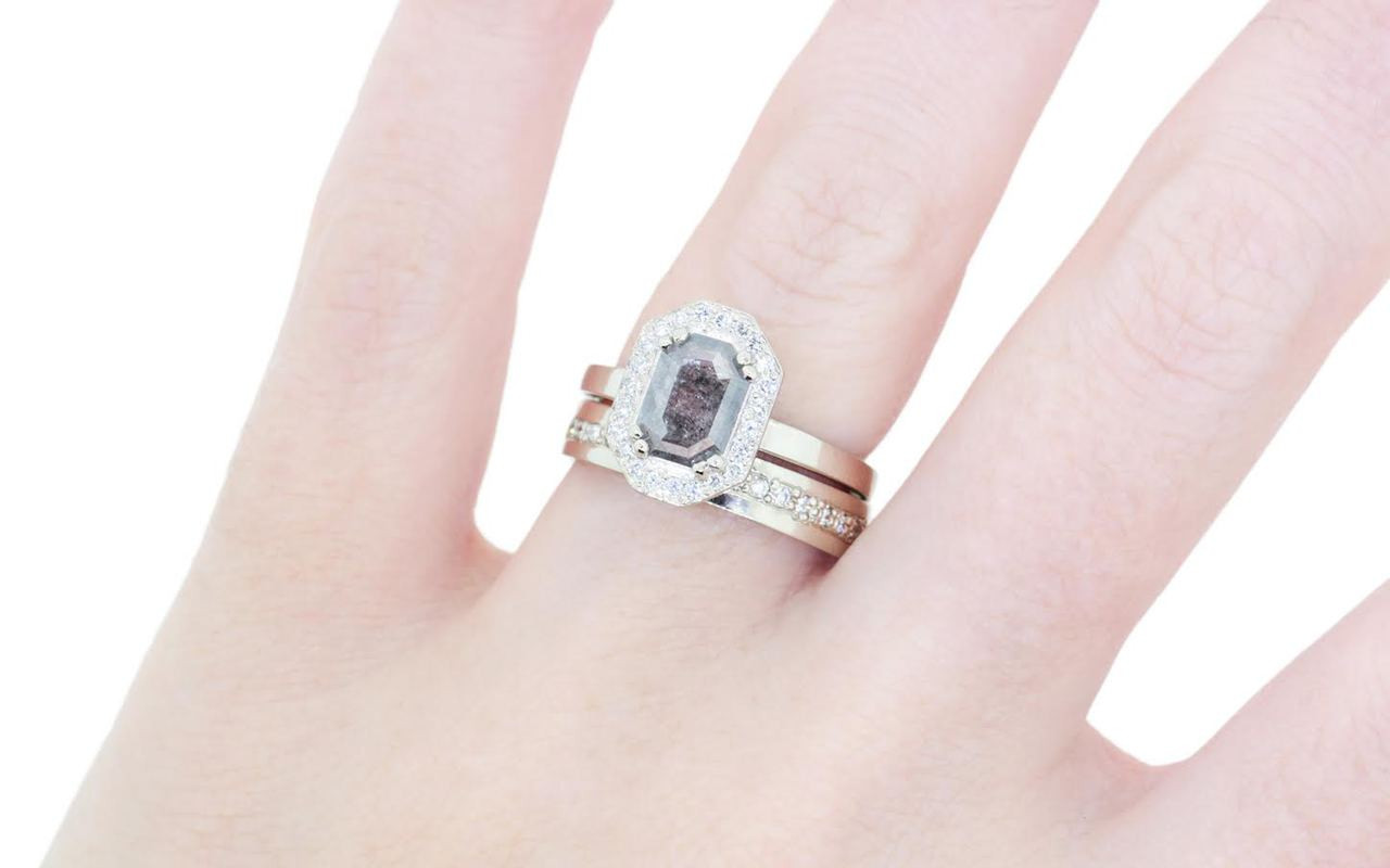 KATLA .66 carat fancy cut salt and pepper diamond prong set in octagon 14k white gold setting with brilliant, white diamonds surround the center diamond in a halo as well as each corner of the setting and each shoulder of the ring.  Modeled on hand with CM 14k white gold eternity diamond wedding band.