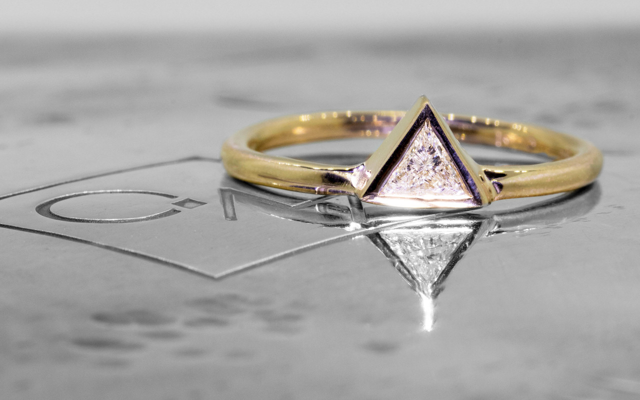 .12 carat trillion white diamond solitaire set in 14k yellow gold.  This gold band.  Front view on metal background with Chinchar/Maloney logo.