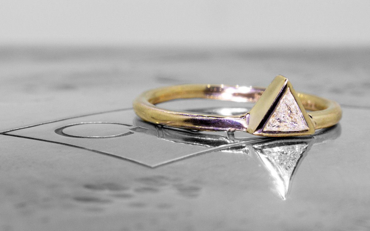 .12 carat trillion white diamond solitaire set in 14k yellow gold.  This gold band.  3/4 view on metal background with Chinchar/Maloney logo.