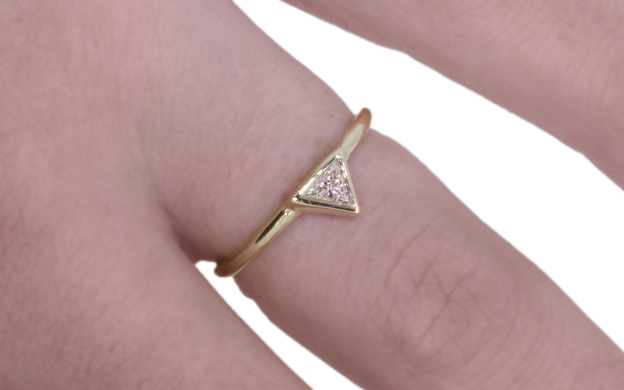 .12 carat trillion white diamond solitaire set in 14k yellow gold.  This gold band.  Modeled on a hand.