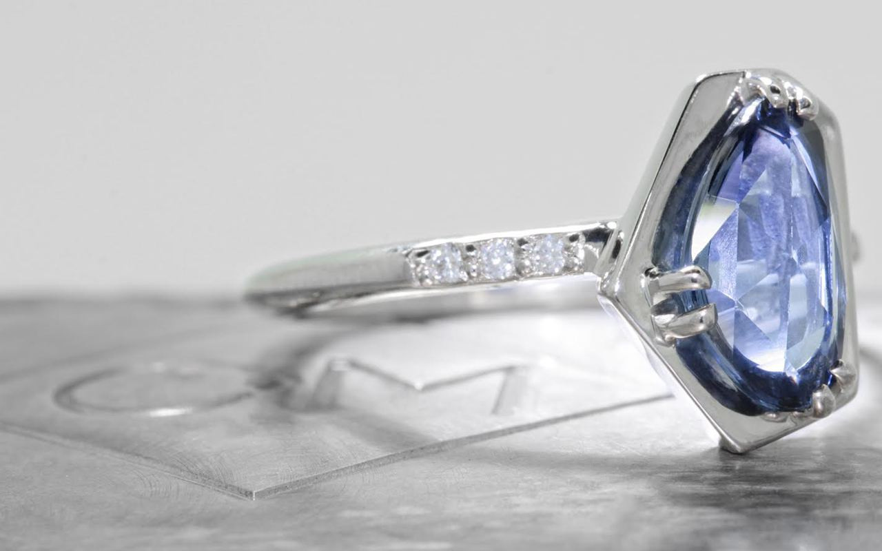 KIKAI 1.88 carat free form rose cut blue sapphire with six 1.2mm brilliant white diamonds set in 14k white gold 1/2 round band. Part of New Classic Collection. 3/4 view on metal background with Chinchar/Maloney logo