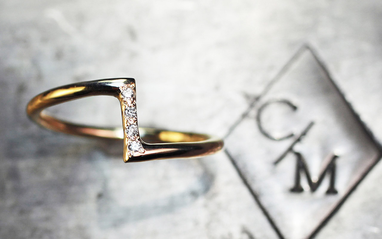 14k yellow gold ring in a zig-zag shape.  Small, brilliant white diamonds are set in the center bar of the ring.  Front view on metal background with Chinchar/Maloney logo.