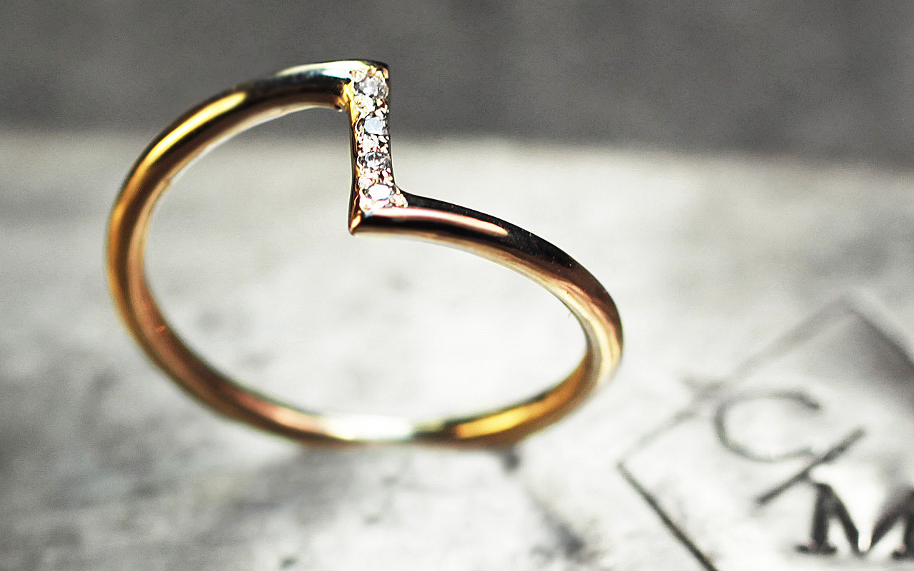 14k yellow gold ring in a zig-zag shape.  Small, brilliant white diamonds are set in the center bar of the ring.  3/4 side view on metal background with Chinchar/Maloney logo.