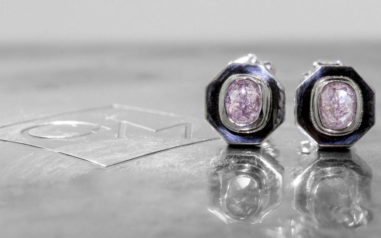 Askja 14k white gold stud earrings. .45 carat pink purple diamonds bezel set in hexagon setting. Shown on metal background with Chinchar/Maloney logo