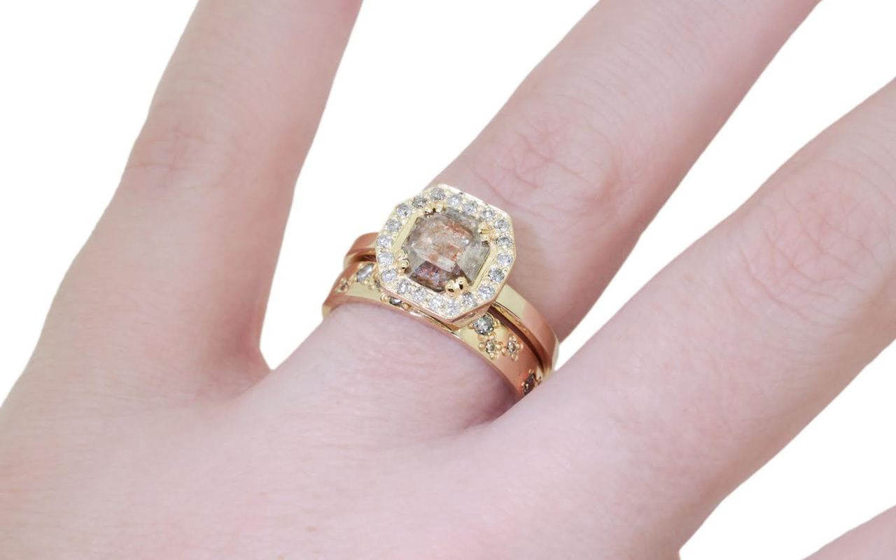 KATLA New Classic .77 carat hexagon cut gray cognac diamond prong set in octagon  14k yellow gold setting with brilliant, gray diamonds surround the center diamond in a halo as well as each corner of the setting and each shoulder of the ring. Shown on hand with organic pave diamond wedding band