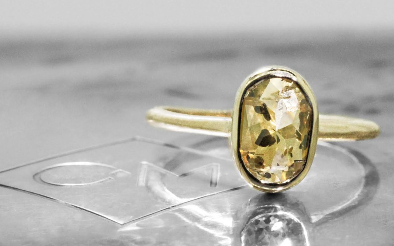2.23 carat oval, rose cut champagne and pepper bezel set diamond ring set in 14k yellow gold 1/2 round band. Front view on metal background with Chinchar/Maloney logo