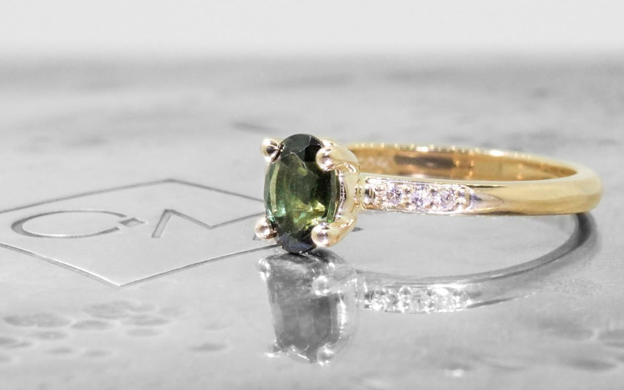 .80 carat green oval faceted tourmaline with six 1.2mm brilliant white diamonds set in 14k yellow gold 1/2 round band. 3/4 view on metal background with Chinchar/Maloney logo