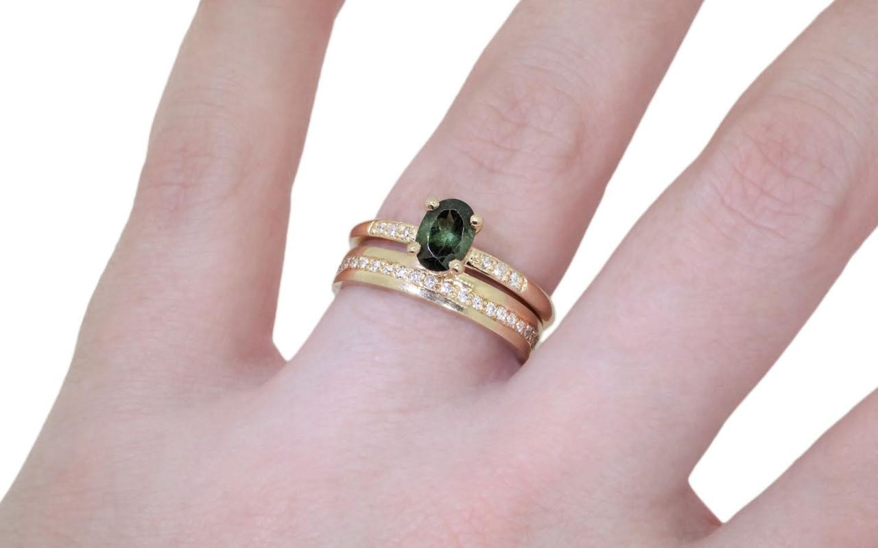 .80 carat green oval faceted tourmaline with six 1.2mm brilliant white diamonds set in 14k yellow gold 1/2 round band. with Eternity wedding band with brilliant white diamonds in 14k yellow gold on a hand